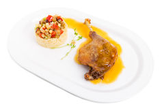 Duck leg confit with couscous and vegetables. Stock Photo