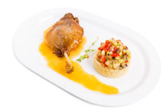 Duck leg confit with couscous and vegetables. Stock Photos