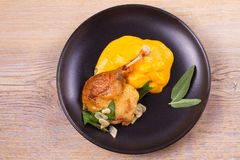 Duck leg with mashed sweet potato, sage and garlic in black plate on wooden background. Duck leg with mashed sweet potato, sage and garlic in black plate on stock photography