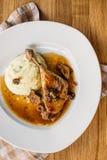 Duck Leg mit Kartoffelpürees mit Soße auf einer hölzernen Stola rustik Art Flache Lage Stockbilder