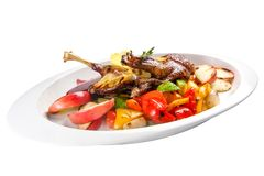 Duck leg with safflowers and grilled vegetables. On a white background stock image