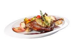 Duck leg with safflowers and grilled vegetables. royalty free stock photography