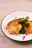 Duck leg with spinach and orange in sweet and sour berry sauce. Royalty Free Stock Photography