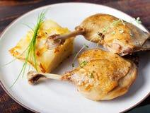 Duck legs confit with potato gratin and mushroom sauce Restaurant serving Stock Image
