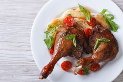 Duck legs roasted with apples and tomatoes  close-up top view Stock Photography