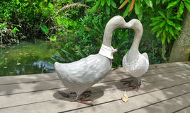 Duck lover couple meeting on the wood pier of river bank. Duck lover couple garden sculpture meeting on the wood pier Royalty Free Stock Image