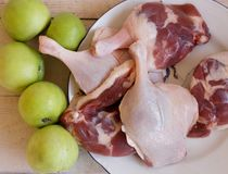 Duck meat fresh, raw duck legs with fruit on a wooden surface. Meat Stock Photos