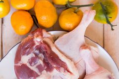 Duck meat fresh, raw duck legs with fruit on a wooden surface. Meat Stock Photography