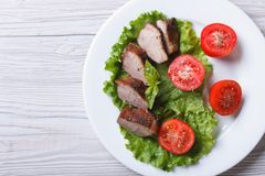 Duck meat fried with tomatoes close-up from above. horizontal Royalty Free Stock Photos