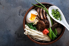 Duck noodles with egg and mushrooms in bowl on dark black stone texture background Stock Photography