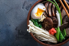 Duck noodles with egg and mushrooms in bowl on dark black stone texture background Royalty Free Stock Photography
