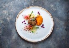 Duck o confit do pé com puré do batat, cenouras e cuscuz, refeição do restaurante imagens de stock royalty free
