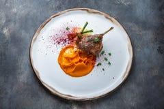 Duck o confit do pé com puré do batat, cenouras e cuscuz, refeição do restaurante fotografia de stock royalty free