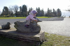 Duck riding. Little girl sitting on a wooden sculpture outdoors Stock Photo