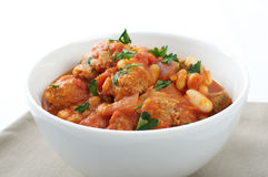 Duck and sausage cassoulet. Duck and pork sausage cassoulet, with cannellini and flageolet beans garnished with parsley royalty free stock images