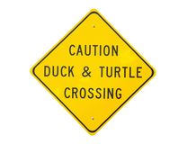 "Duck and turtle crossing sign. Yellow diamond shaped highway style sign with text ""caution duck and turtle crossing"" white background Royalty Free Stock Photos"
