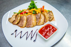 Duck with vegetables and sauce on a plate. Duck meat with red sauce and vegetable ragout Royalty Free Stock Photography