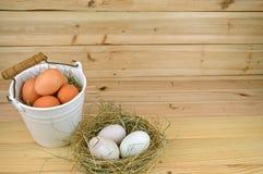 Ducken Sie Eier in einem Nest und Hühnereien in einem keramischen Korb Lizenzfreie Stockbilder