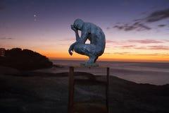 Duckende denkende Mann Skulptur durch das Meer, Bondi Lizenzfreie Stockfotos