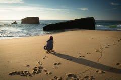 Duckende junge Frau auf dem szenischen sandigen Strand, der Fotos des Kriegsblockhauses in Atlantik macht Stockfoto