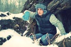 Duckender stattlicher junger Mann im Winter stockfotografie