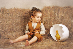 Duckling in the shell and a beautiful, curly boy. Beautiful curly-haired boy sitting next to hay and looking at duckling who emerges from the shell Royalty Free Stock Photo