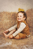 Duckling is sitting on the head of curly boy. Curly-haired boy sitting next to hay and laughing with duck on head Stock Image