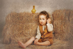 Duckling standing on hay, and the boy holding an egg and ear listening Stock Photo