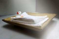 Duckling on a towel in a hotel. Small ceramic duck on a towel at the hotel Royalty Free Stock Photography