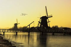 Warm and frozen windmill sunrise Royalty Free Stock Photo