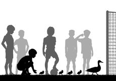 Ducks stop play. Editable vector silhouette illustration of a family of ducks stopping boys playing football Stock Photos