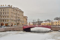 Ducks swim in ice-hole under the Red bridge over the Moika river Royalty Free Stock Photography