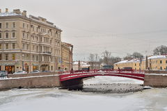 Ducks swim in ice-hole under the Red bridge over the Moika river Stock Photos