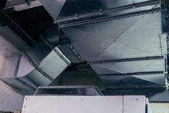 Duct, ductwork, ventilation, air conditioning, industrial, modern, metallic. Close-up view of the modern big dimensions ductwork installed on the ceiling of the royalty free stock photo