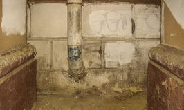 Duct from the dungeon. S, tin pipe on a dilapidated wall between two columns in the archway of a house royalty free stock image