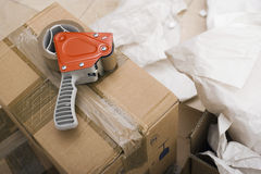 Duct tape dispenser on top of sealed cardboard box, paper on floor, close-up Stock Photo