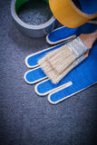 Duct tape paintbrushes protective gloves on black. Background construction concept stock images