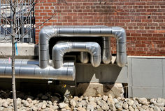 Ductwork. Insulated heating and air conditioning pipes on building exterior stock image