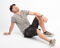 Dude laughing on floor. Young Caucasian dude sitting on floor wearing cap and in casual urban outfit leaning backwards with a big smile. Full body shot. White stock photography