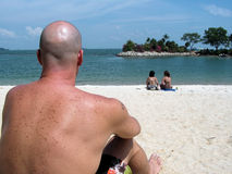 Dude with a view at beach. Sunbathing at a beach on the equator.  The view is of a lagoon that connects to the sea Royalty Free Stock Photos