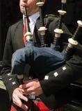 Dudelsackpfeifer, der seine Rohre durchbrennt Lizenzfreie Stockbilder