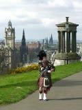 Dudelsackpfeifer in Edinburgh, über dem Stadtbild Lizenzfreies Stockfoto