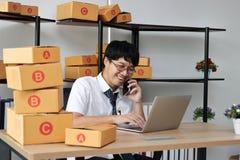 Dueño asiático joven del empresario que habla en el teléfono en el lugar de trabajo en casa Cree la pequeña empresa fotografía de archivo
