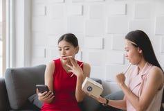 Dueño chocado de dos mujeres que elabora en la oficina de la casa, sme femenino en línea, pequeña empresa del empresario del comi imagen de archivo libre de regalías
