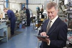 Dueño de la fábrica de ingeniería usando la tableta de Digitaces con el personal adentro Imagen de archivo