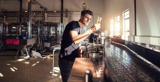 Dueño de la fábrica de la cervecería que examina la calidad de la cerveza del arte imagenes de archivo