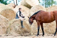 Dueño de la muchacha que se sienta cerca de su caballo en pila del heno Foto de archivo