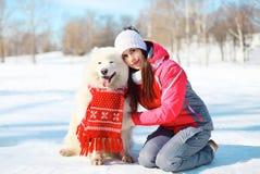 Dueño de la mujer con el perro blanco del samoyedo junto en nieve en invierno Imagen de archivo