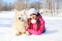 Dueño de la mujer con el perro blanco del samoyedo que miente en nieve en invierno Fotografía de archivo
