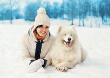 Dueño de la mujer con el perro blanco del samoyedo que miente en nieve en invierno Imagen de archivo